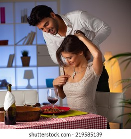 Romantic couple having dinner at home. Man offering chocolate to woman.