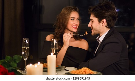 Romantic couple having romantic dinner in restaurant, feeding each other.