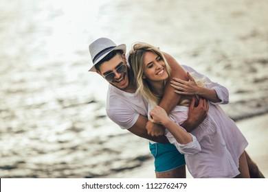Romantic couple having fun on the beach. Happy couple running on beach at sunset.