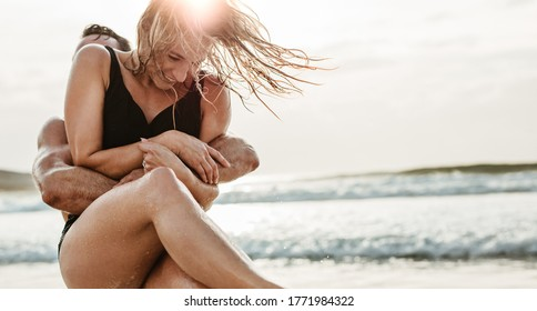 Romantic couple having fun on the beach. Man and woman playing and enjoying themselves on the beach.