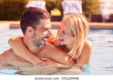 Romantic Couple Having Fun On Summer Vacation Relaxing In Outdoor Swimming Pool
