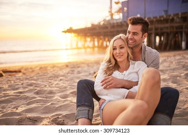 romantic couple having fun at santa monica on beach at sunset