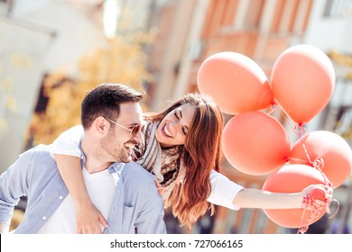 Romantic couple having fun while walking in the city. Girl is sitting piggyback and holding balloons.