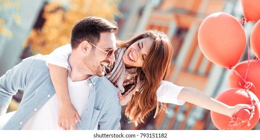 Romantic couple is having fun while walking in the city.Girl is sitting piggyback and holding balloons.