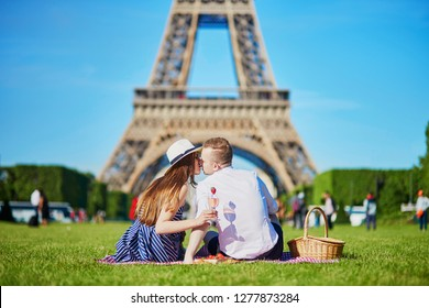 Romantic couple having picnic on grass with wine and fruits near the Eiffel tower in Paris