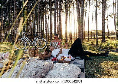 Romantic couple having a picnic at sunset near forest