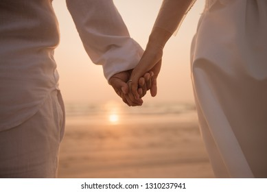 Romantic couple holding hand against the sea at sunset.