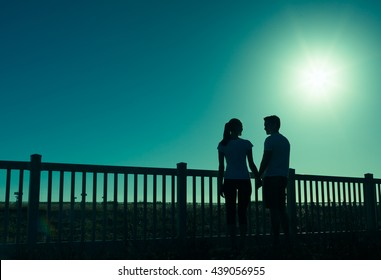 Romantic couple holding hands with a full moon glowing in the distance.