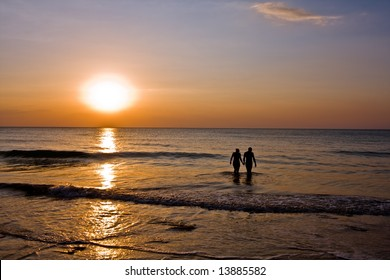 romantic couple holding hands in the ocean at sunset