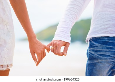 Romantic couple holding hands on a beach in sunset.