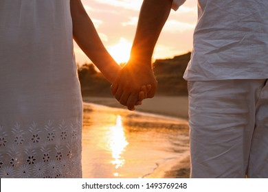 Romantic couple holding hands together on beach, closeup view