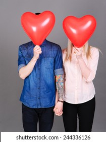 Romantic couple holding heart balloons over gray. Love concept. Valentines day.
