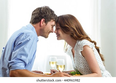 Romantic couple holding wineglasses at home