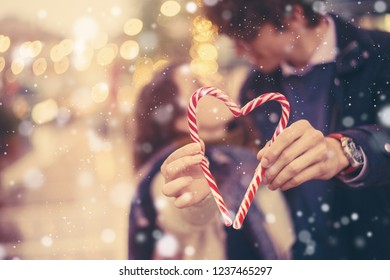 Romantic couple holds a holiday christmas candy cane heart. Bokeh lights in background, snow falling effect, vintage toning