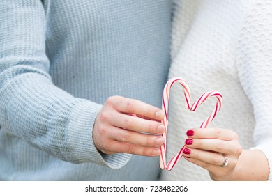 Romantic couple holds a holiday christmas candy cane heart