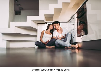 Romantic couple at home. Attractive young woman and handsome man are enjoying spending time together. Sitting on the floor in light modern kitchen with cup of coffee in hands.