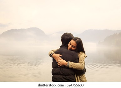 Romantic couple hugging by misty lake in autumn