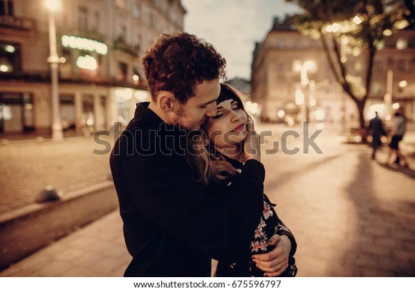 Romantic couple hugging in evening Paris street, handsome bearded man holding beautiful blonde woman in black floral dress outdoors, couple portrait, city lights in the background
