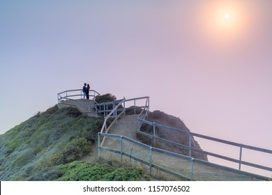 Romantic couple hugging in foggy sunset Muir Beach Overlook. Muir Beach, Marin County, California, USA.