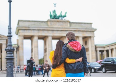 Romantic couple hugging and looking to Brandenburg tor famous gate in Berlin city, Germany together.Happy family travel concept