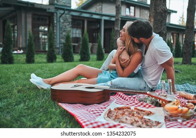 Romantic couple hugging while having picnic. Handsome bearded man and attractive young woman are sitting together on grass on the backyard.