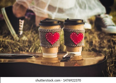 Romantic couple hugging while having picnic in sunset light. Coffee cup cozy knitted sleeve with felt red heart.
