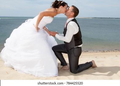 romantic couple kiss in wedding dress on the beach