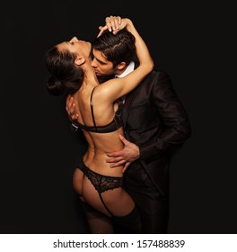 Romantic couple kissing and cuddling with the woman in erotic lacy black lingerie being fondled and kissed by a handsome man in a suit, dark suggestive portrait