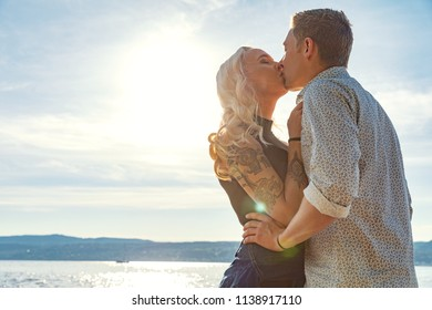 Romantic couple kissing and embrace on beach a sunny day