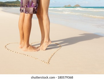 Romantic couple kissing on the beach. Love - male and female feet in the heart on the beach.