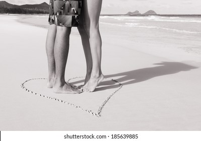Romantic couple kissing on the beach. Love - male and female feet in the heart on the beach. Black and white image.