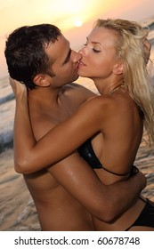 Romantic couple kissing on a beach at sunset
