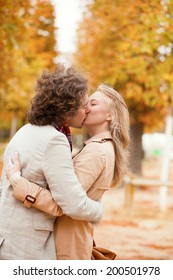Romantic couple kissing on a beautiful fall day