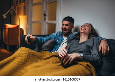 romantic couple laying sofa in their living room watching movie on television