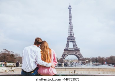 romantic couple looking at Eiffel tower in Paris, honeymoon background