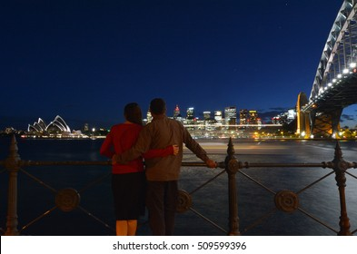 A romantic couple looks at Sydney skyline at dusk in Sydney New South Wales, Australia.