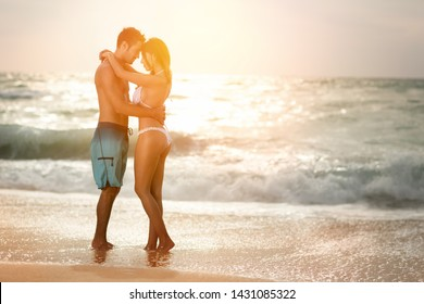 Romantic couple in love embracing on the beach at sunset