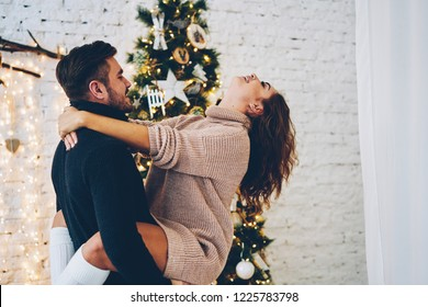 Romantic couple in love feeling joy while celebrating New Year day together, handsome man hugging his girlfriends spending winter vacation in cozy home with decorated traditional christmas tree