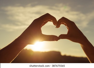 Romantic couple in love gesturing a heart with fingers on the sunset