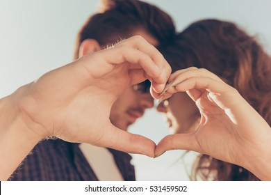 Romantic couple in love gesturing a heart with fingers