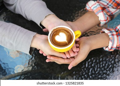 Romantic couple in love hand holding two cups of latte art with pattern the heart on table in coffee shop