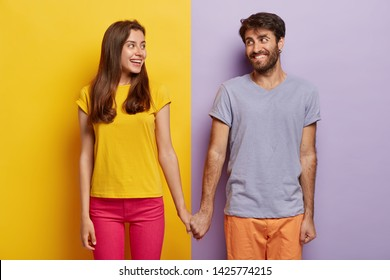 Romantic couple in love have date, hold hands, look positively at each other, feel support, walk together. Positive man poses over purple background, woman on yellow. Contrast. Relationship concept