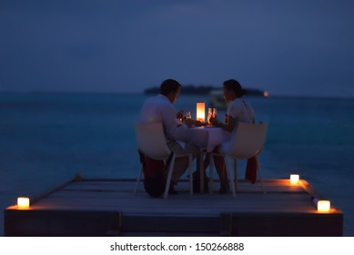 romantic couple  in love have dinner in outdoor restaurant with candles with sea in background