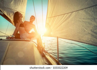 Romantic couple in love on sail boat at sunset under sunlight on yacht - Happy exclusive alternative lifestyle concept - Love story of two caucasian young people.