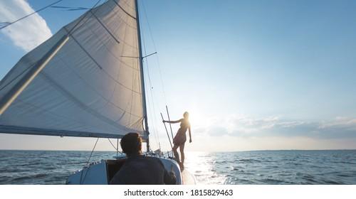 Romantisches Paar verliebt auf Segelboot bei Sonnenuntergang auf der Yacht, A Mann und eine Frau reisen auf einer Segelyacht.