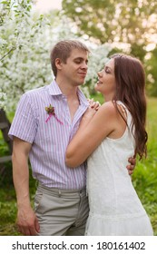 A romantic couple in love outdoors among the trees in blossom. Celebrating anniversary of their wedding day.