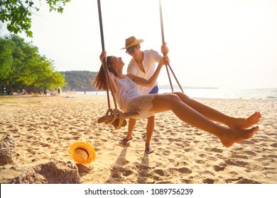 Romantic couple in love playing together on rope swing at summer beach for fun and happy smile. young man and woman on holidays or honeymoon