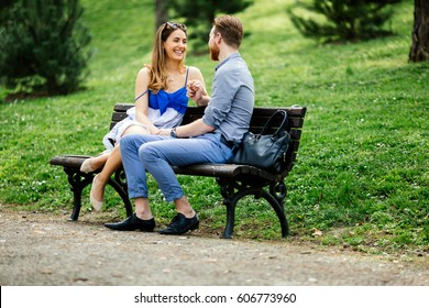 Romantic couple in love sitting on park bench
