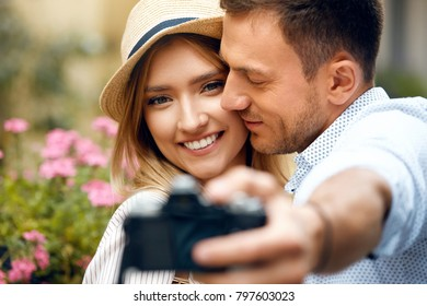 Romantic Couple In Love Taking Photos On Street. Beautiful Smiling Man And Woman Taking Photos Of Themselves Using Camera Outdoors. Relationships Concept. High Quality Image.