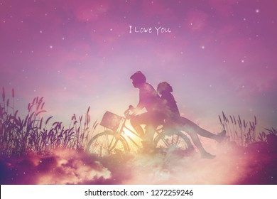 Romantic couple in love with their bicycle on field,dreaming about the stars in night sky.